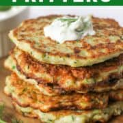 greek zucchini fritters stacked on top of each other on a wooden board.