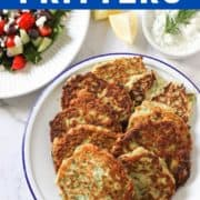 a plate of greek zucchini fritters surrounded by greek salad and tzatziki dip.
