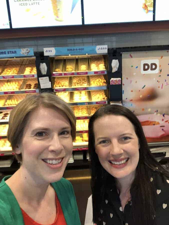 two women standing in front of a donut stand.