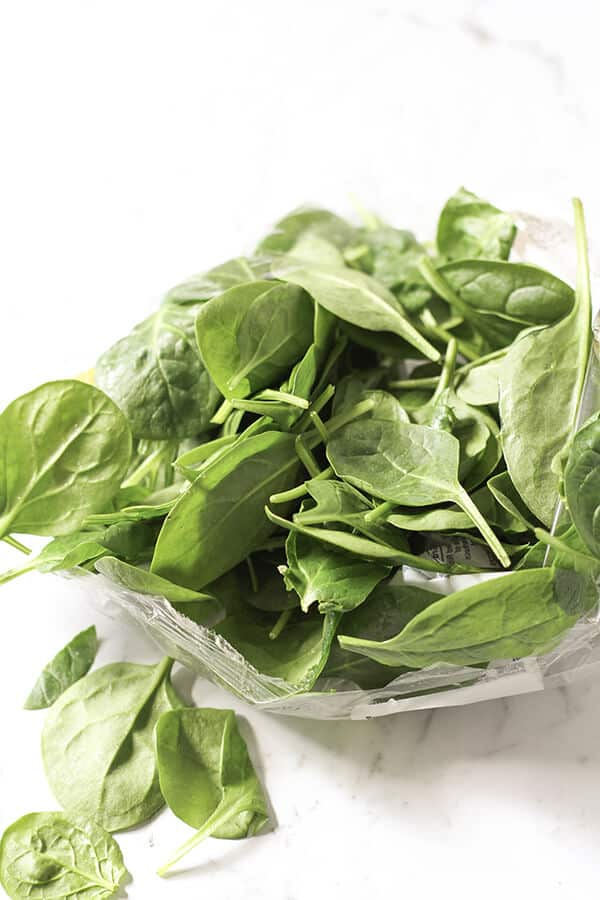 loose baby spinach leaves spilling out of a packet