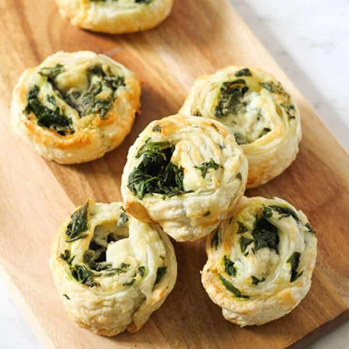 spinach and feta pinwheels on a wooden serving board.
