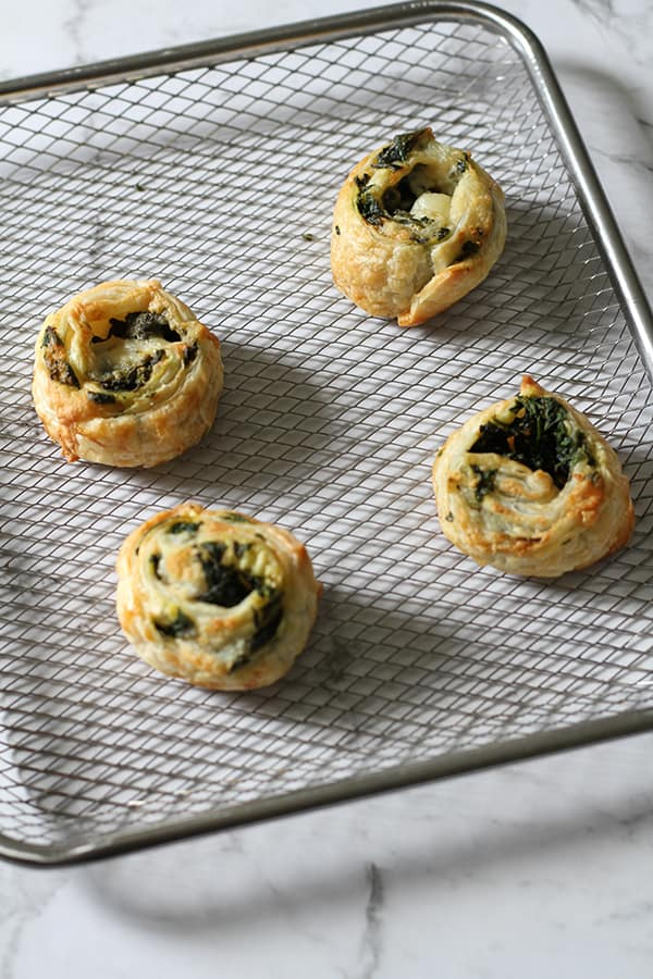 spinach and feta pinwheels on an air fryer tray.
