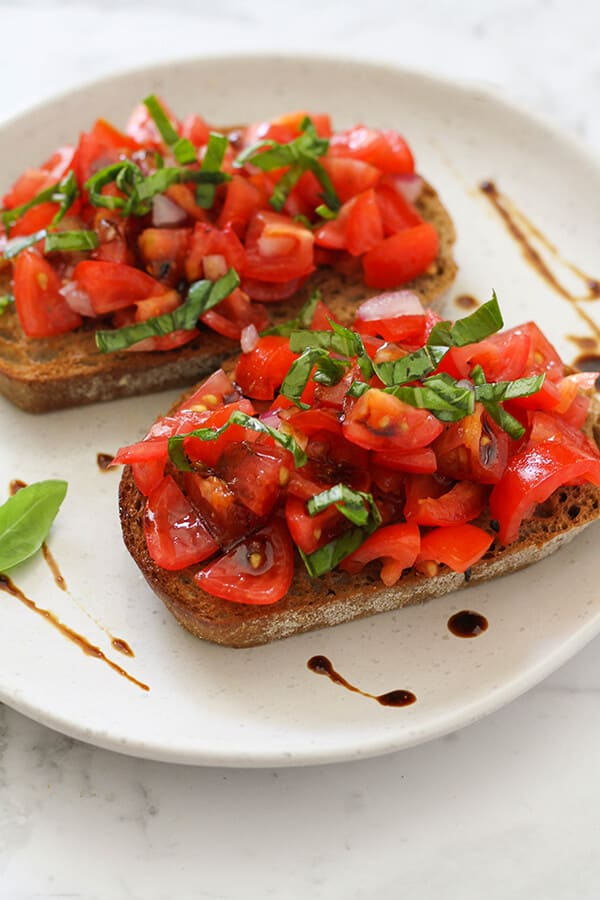 two pieces of brushetta on a white plate covered in balsamic glaze.