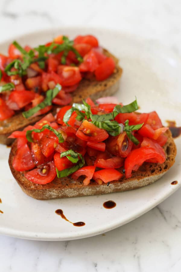 two pieces of bruschetta on a white plate covered in balsamic glaze.
