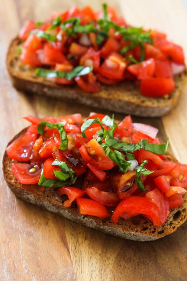 two pieces of bruschetta on a wooden board covered in balsamic glaze.