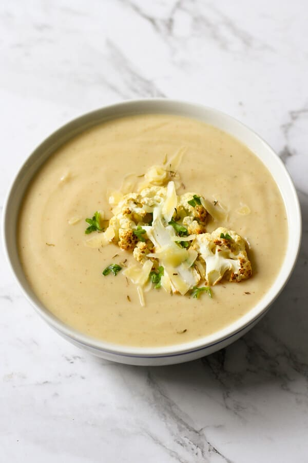 a bowl of cauliflower soup with roasted cauliflower, shredded cheese and parsley on top.