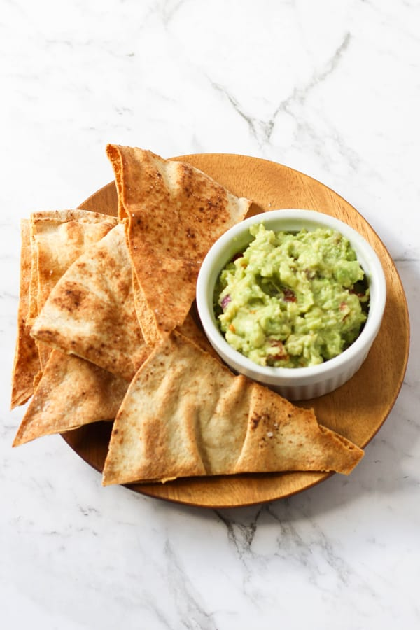 pita chips on a wooden plate with guacamole.