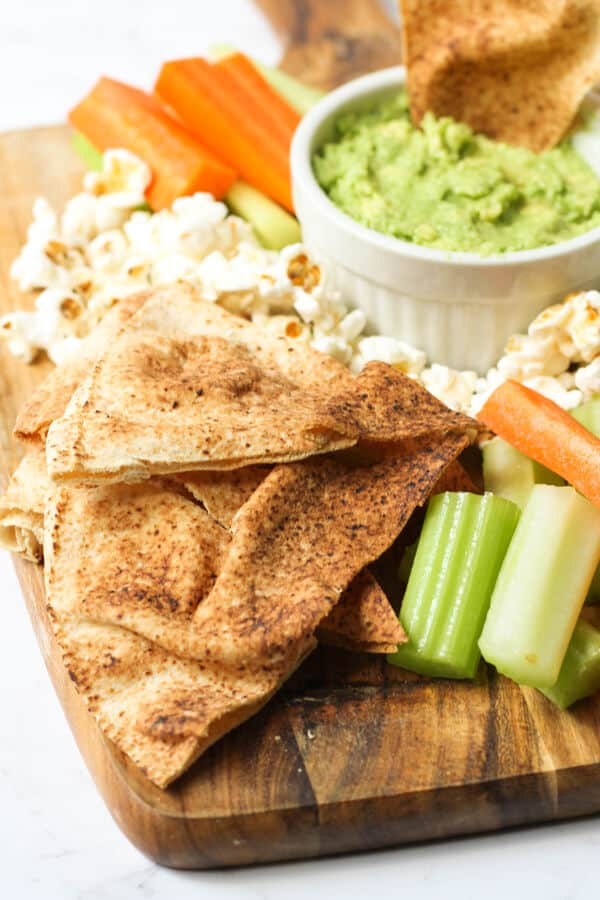 pita chips on a serving board with guacamole, carrots, cucumber and popcorn.