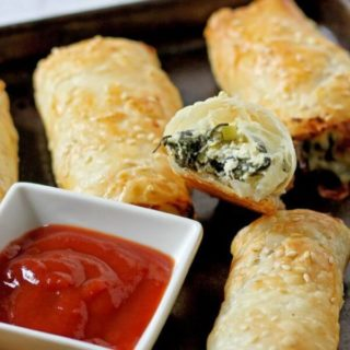 spinach and ricotta rolls on a baking tray.