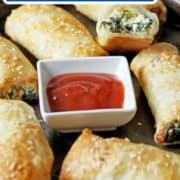 """spinach and ricotta rolls on a baking tray with text overlay """"spinach and ricotta 'sausage' rolls""""."""