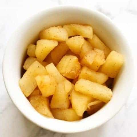stewed cinnamon apple pieces in a white bowl.