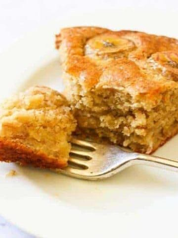 a slice of banana cake on a white plate.
