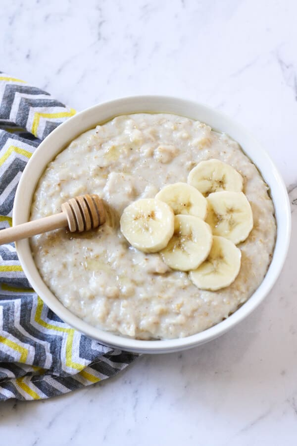 a bowl of oatmeal topped with banana slices and honey.