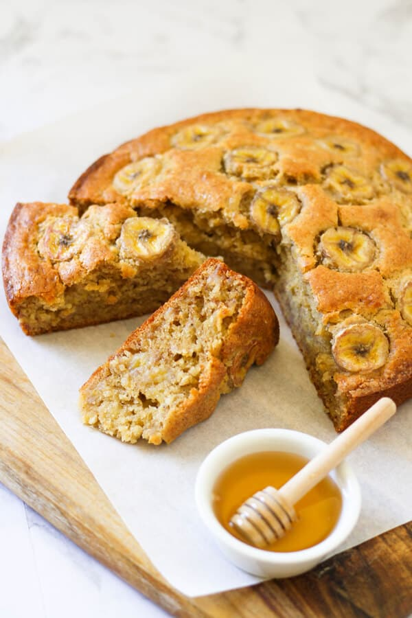 banana cake on a wooden board with a small bowl of honey.