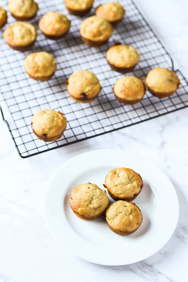 3 mini banana muffins on a white plate with a cooling rack of muffins in the background.