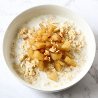 a bowl of oatmeal topped with stewed apple and almonds.