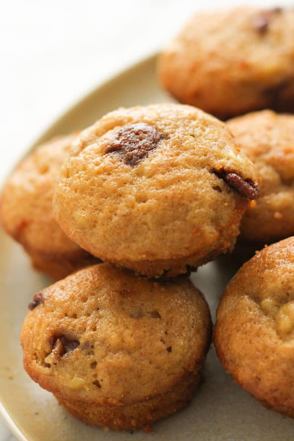 mini banana muffins stacked on a plate.