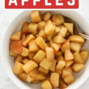 "diced apple pieces in a bowl with text overlay ""stewed cinnamon apples""."