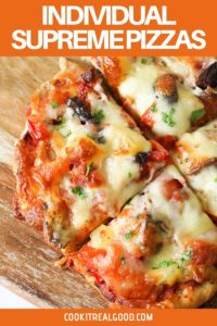 Supreme pizza on a wooden chopping board,