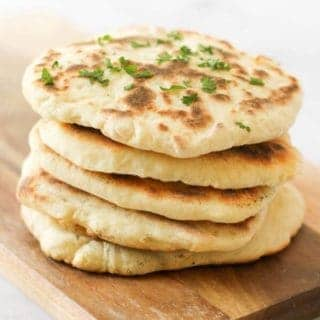 yoghurt flatbreads stacked on top of each other on a wooden board.
