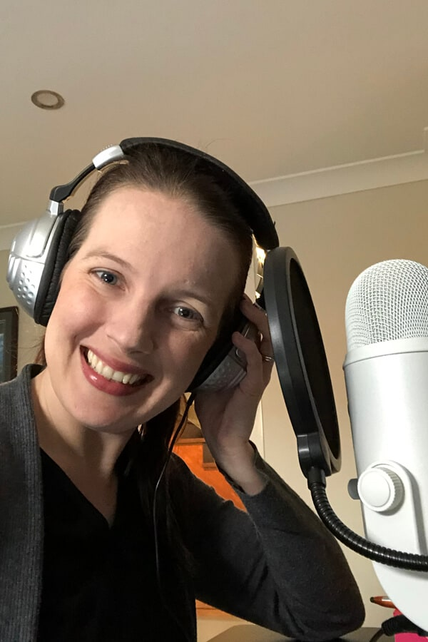 Brunette woman wearing headphones and talking into a microphone.