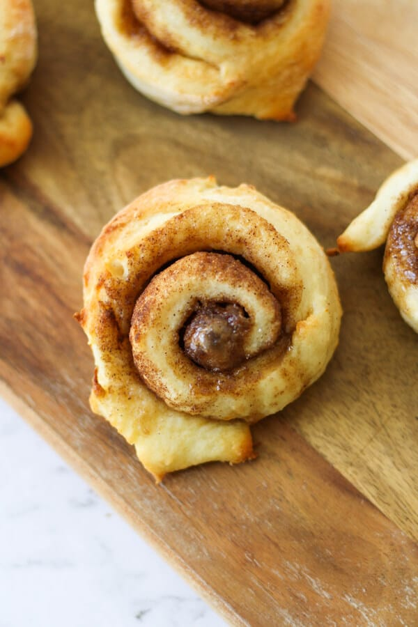 freshly baked cinnamon scrolls on a wooden board.