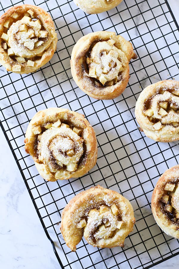 apple and cinnamon scrolls sitting on a cooling rack.