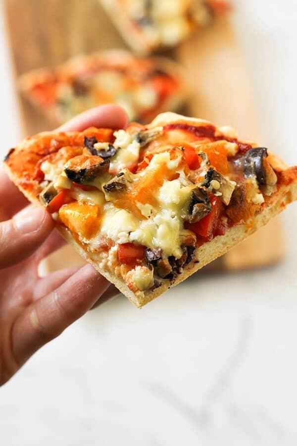 A hand holding a slice of Roast Pumpkin Pizza.
