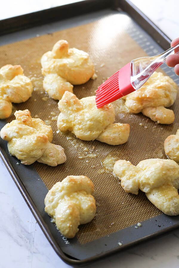 garlic knots on a baking tray being brushed with garlic butter.