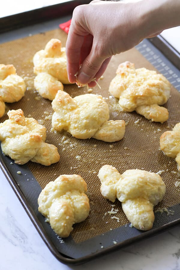 garlic knots on a baking tray being sprinkled with parmesan cheese.
