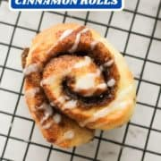 "cinnamon roll on a wire rack covered with glaze with text overlay ""no yeast cinnamon rolls""."