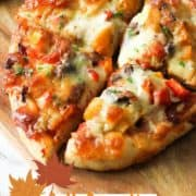 """pizza on a wooden board with text overlay """"fall favorite roast pumpkin pizza""""."""
