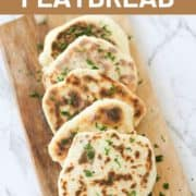 flatbreads laid out on top of a wooden board.