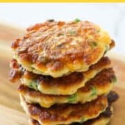 Pea & Sweet Corn Fritters in a stack on a wooden board.