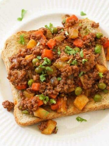 Savoury mince on top of a piece of toast on a white plate.