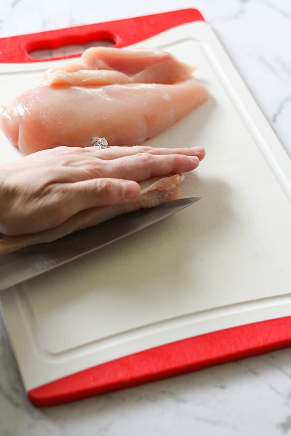 Chicken breast being cut in half.