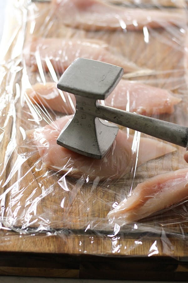 chicken breast on a wooden cutting board being tenderised with a meat mallet.