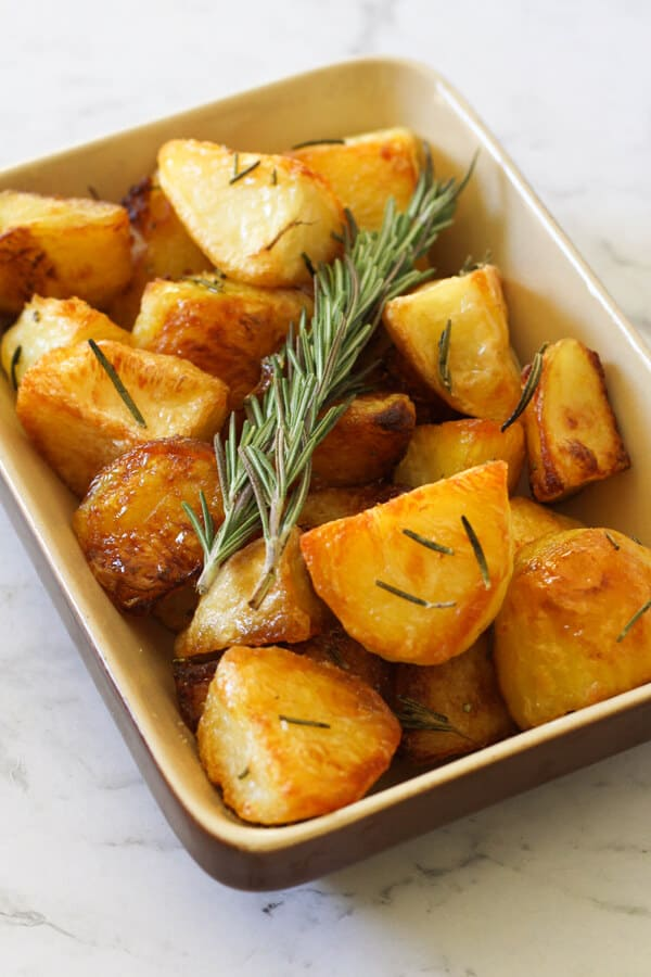 Crispy roast potatoes in a serving tray with rosemary sprigs on top.