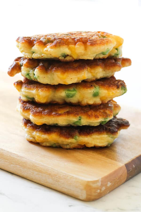 Pea & Sweet Corn Fritters stacked on top of each other on a wooden board.