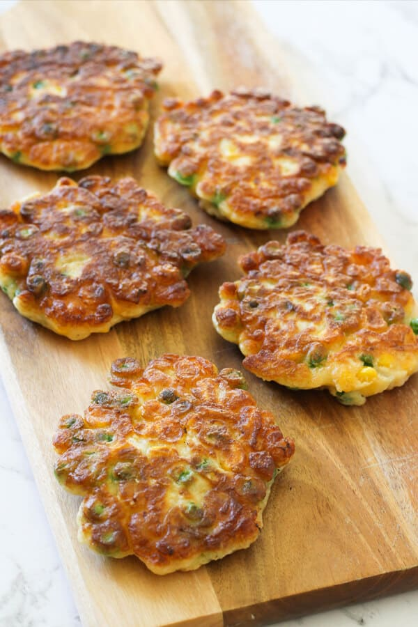 Pea & Sweet Corn Fritters on a wooden board.