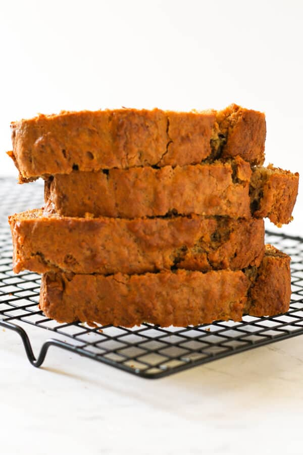 Banana bread slices stacked on a wire cooling rack.