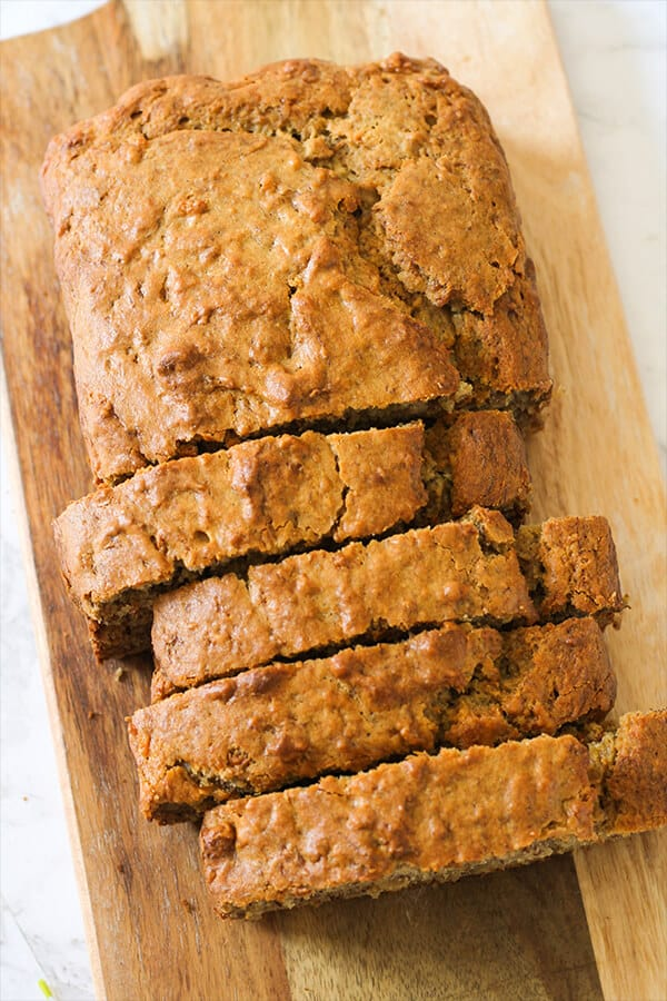 Sliced buttermilk banana bread laying on a wooden board.