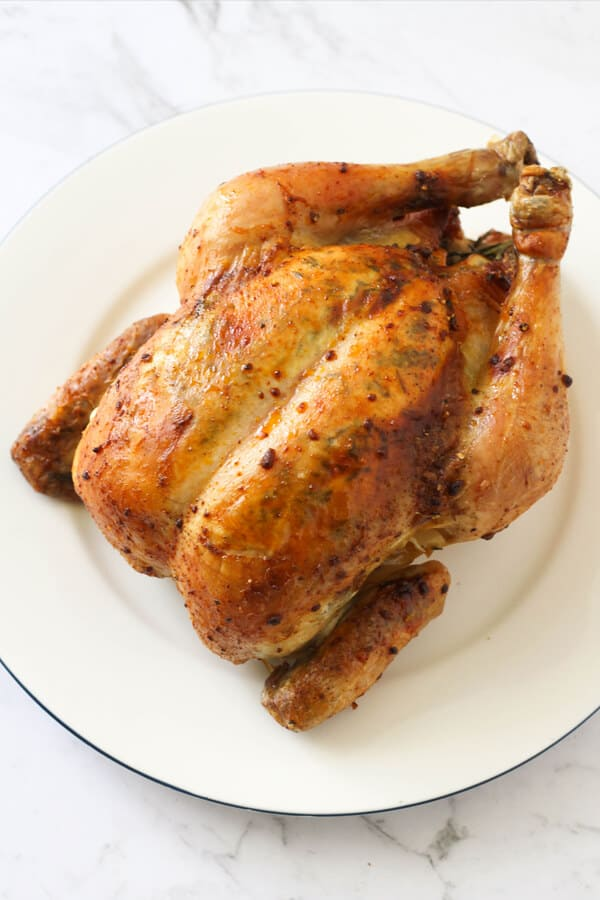 Whole roast chicken on a white plate.