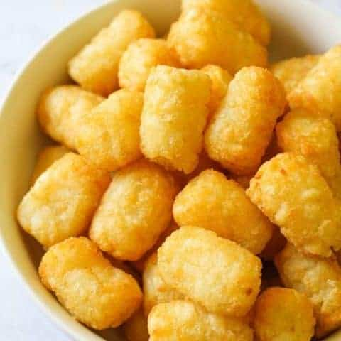 A white bowl filled with crispy tater tots.