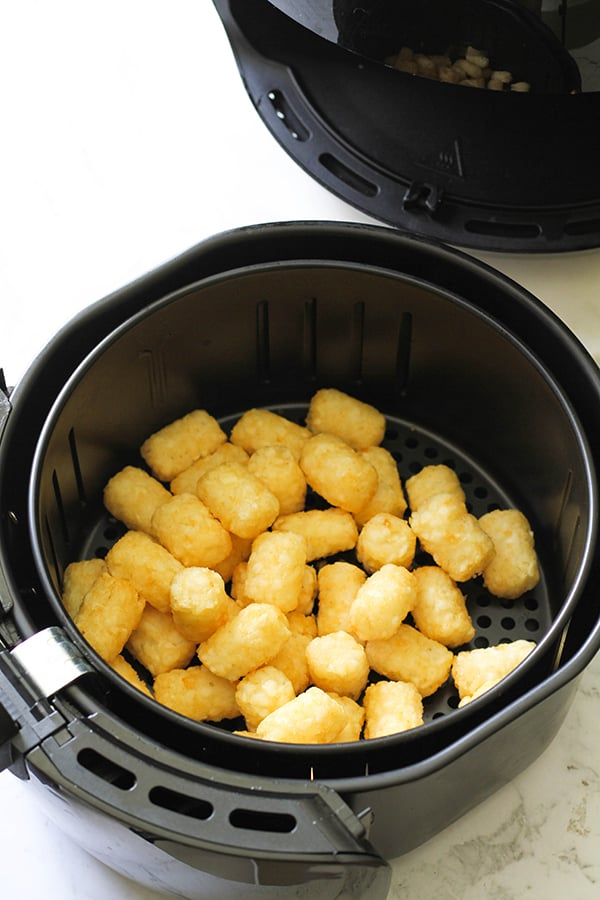 Air fryer basket filled with tater tots.