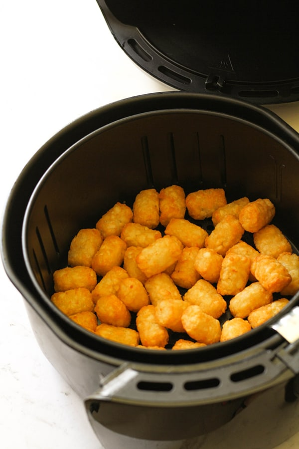 Air fryer basket filled with crispy tater tots.