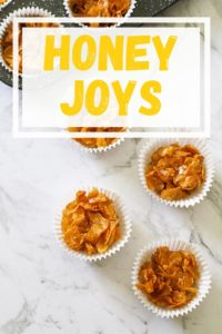 Honey joys in white paper liners on a marble background.