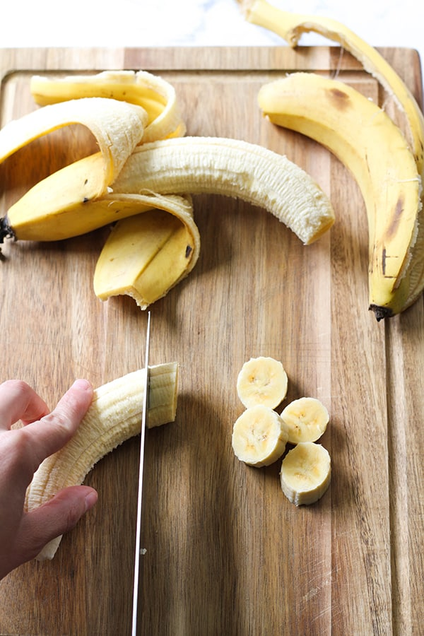 banana being sliced on a wooden cutting board.