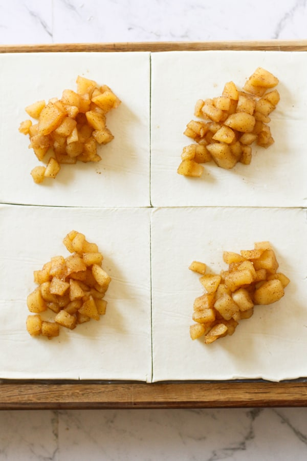 puff pastry cut into squares with spoonfuls of diced apple in the centre.
