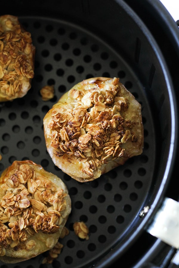 cooked baked apples in an air fryer basket.